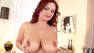 Redhead hot milf Sirale enjoys in playing with her big and really arousing boobs in front of the camera after she takes her clothes off and has fun in bedroom
